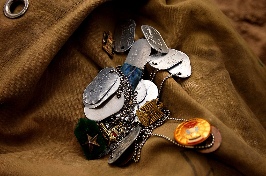 A collection of Iraqi soldiers dog tags and pins are collected at a makeshift cemetery at Baghdad International Airport on April 9, 2003. Operation Iraqi Freedom is the multinational coalition effort to liberate the Iraqi people, eliminate Iraq's weapons of mass destruction and end the regime of Saddam Hussein. — © SSgt. Jeremy T. Lock/