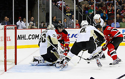 Dec 10, 2008; Newark, NJ, USA; New Jersey Devils center Travis Zajac (19) and New Jersey Devils left wing Zach Parise (9) battle against Pittsburgh Penguins defenseman Rob Scuderi (4) after a save by Pittsburgh Penguins goalie Dany Sabourin (30) during the second period at the Prudential Center.