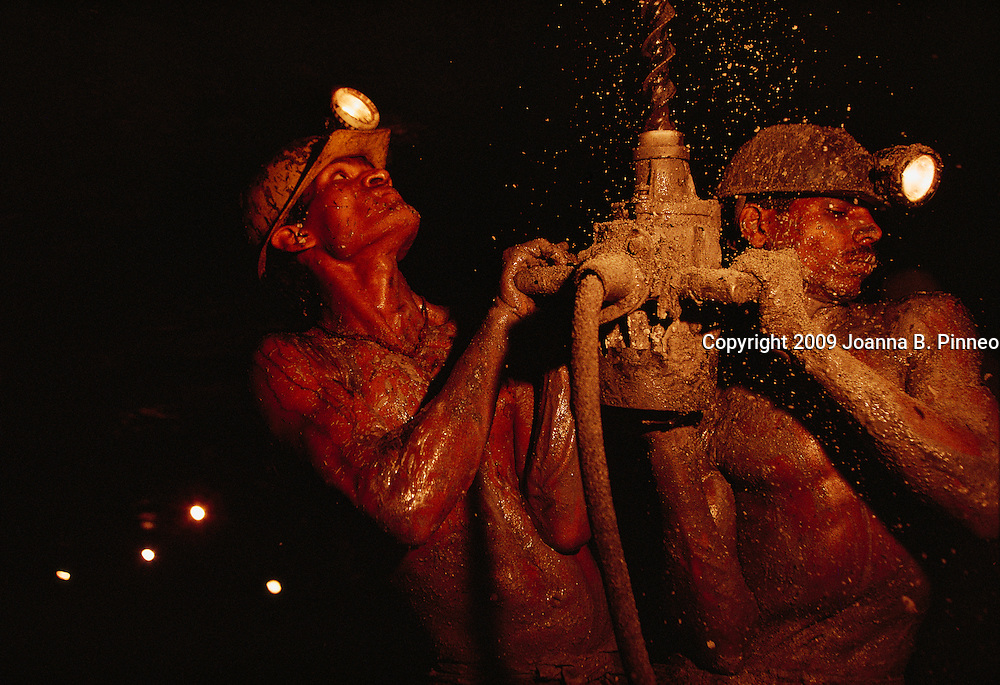Miners in India drill to set a dynamite charge.