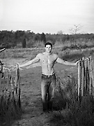 handsome shirtless man in jeans standing by a beach fence in East Hampton, NY