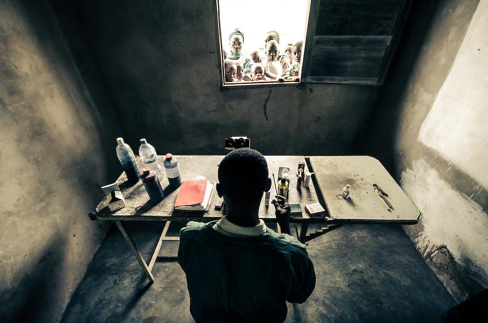 A laboratory technician works in a rural clinic near Mbuji-Mayi, DRC.