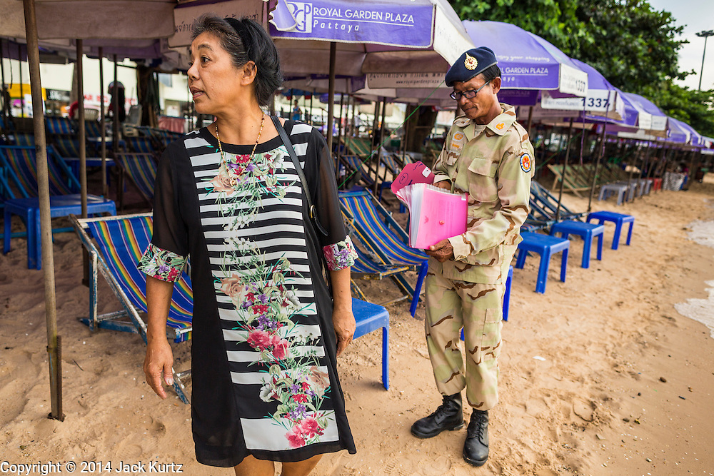 "26 SEPTEMBER 2014 - PATTAYA, CHONBURI, THAILAND: A defense volunteer talks to a business owner who rents beach umbrellas to tourists in Pataya. Pataya, a beach resort about two hours from Bangkok, has wrestled with a reputation of having a high crime rate and being a haven for sex tourism. After the coup in May, the military government cracked down on other Thai beach resorts, notably Phuket and Hua Hin, putting military officers in charge of law enforcement and cleaning up unlicensed businesses that encroached on beaches. Pattaya city officials have launched their own crackdown and clean up in order to prevent a military crackdown. City officials have vowed to remake Pattaya as a ""family friendly"" destination. City police and tourist police now patrol ""Walking Street,"" Pattaya's notorious red light district, and officials are cracking down on unlicensed businesses on the beach.     PHOTO BY JACK KURTZ"