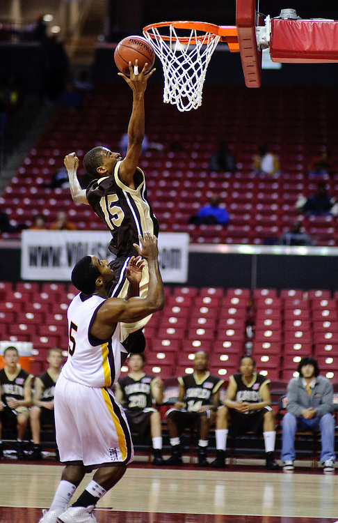 (staff photo by Matt Roth)..Owings Mills's Thomas Malcolm reaches reaches for the net over Dunbar's Nathan Ayers. Owings Mills lost to Dunbar 64-53 in the 1A state Championship game at The University of Maryland's Comcast Center Saturday, March 13, 2010.