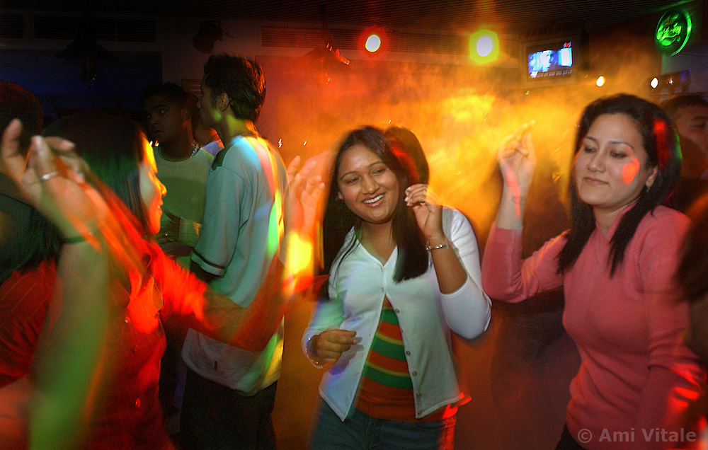 Nepalese teenagers dance in a nightclub in Katmandu, seemingly unaware of the brutal conflict that lies just outside the city in Nepal March 5, 2005. (Ami Vitale)