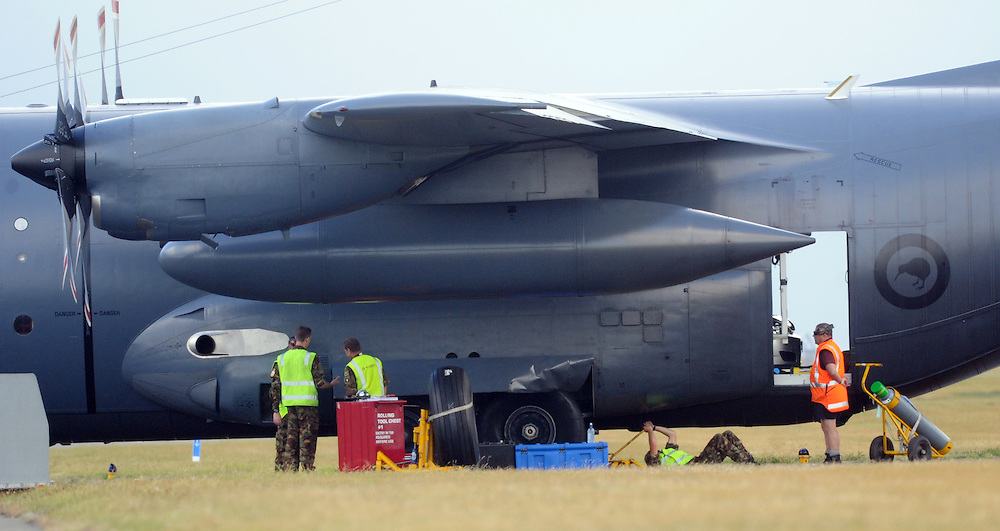 Air Force engineers replace a tyre on a RNZAF C31 Hercules after it blew the tyre on landing at the Wellington Airport and was moved from the runway to a taxiway for the repair, Wellington, New Zealand, Monday, March 17, 2014. Credit:SNPA / Ross Setford