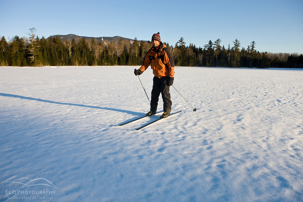 A man cross-country skiing on a frozen pond near Little Lyford Pond Camps near Greenville, Maine, Winter.  Baker Mountain is in the distance.