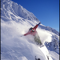A snowboarder slashes the powder pillow on top of a rock on Blackcomb Mountain. Whistler, BC, Canada.
