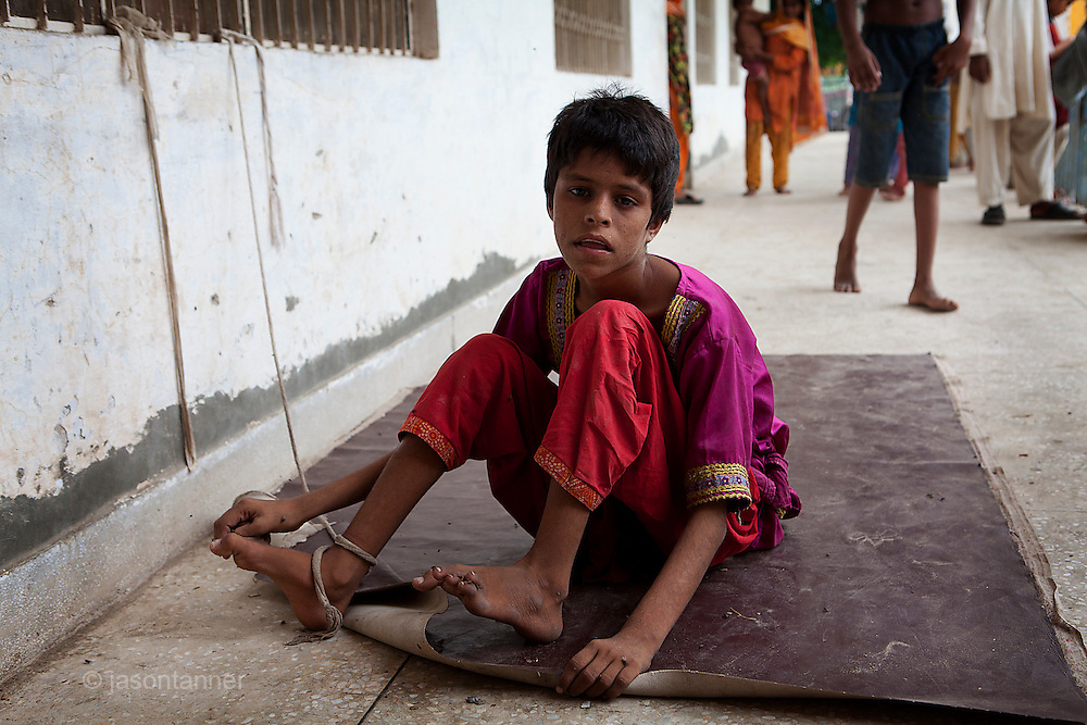 Muzzafargarh: Sidrah, a 12 year old mentally disabled girl is restrained by a leash to her ankle tied to metal bars on a window. Two years ago she was orphaned after the death of her parents from drug overdose. ..Sidrah escaped the flooding with her grandmother and arrived at the makeshift camp on 2nd August. Unfortunately her grandmother died at the IDP camp on 5th August, once again leaving her orphaned. ..Administrators at the camp say she has been tied up for her own safety. Although general doctors are providing medical services at the camp they say they are not qualified to offer Sidrah the assistance she needs...A Government Boys School acting as a Flood Relief Camp in Munda Chowk...Doctors working at the camp estimate some 5000 people have arrived in the makeshift camp in last 2 weeks. Field kitchens prepare food and there is a supply of clean water for those displaced by the flooding..
