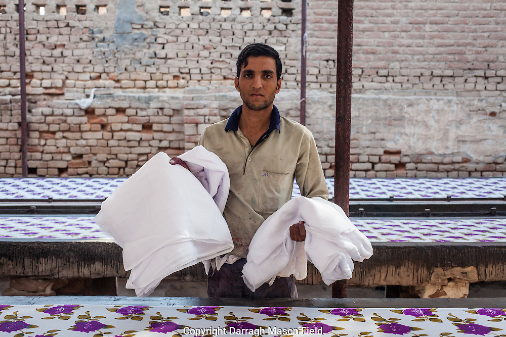 A worker brings out new sheets of fabric to be printed.