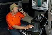 Trucker David Maloney, 23, of Aledo, Texas, downs an energy drink as he goes online using WiFi access Tuesday, March 30, 2004, in the parking lot of the Flying J Travel Plaza in Waddy, Ky. (AP Photo/Brian Bohannon)