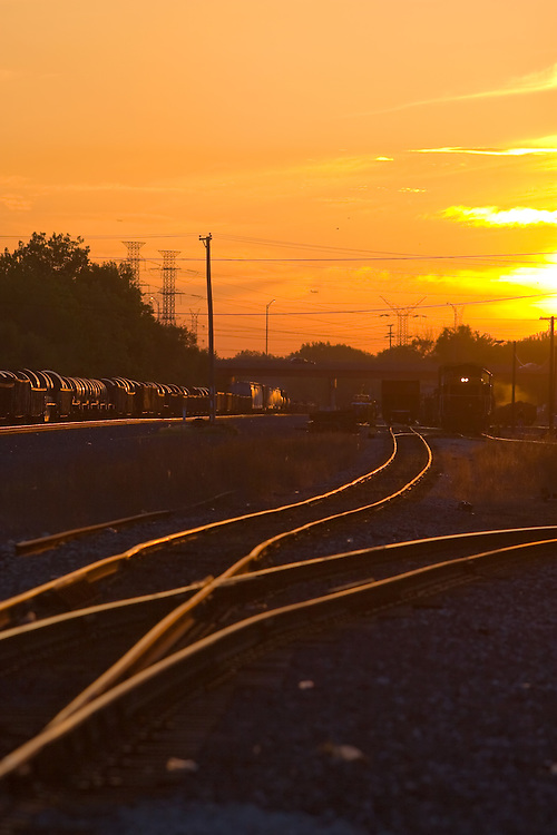 The sun sets over the Indiana Harbor Belt's State Line Yard in Hammond, IN as a train of coiled steel heads east.