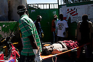 A woman with cholera symptoms is carried into a medical clinic on Tuesday, November 23, 2010 in the Cite Soleil neighborhood of Port-au-Prince, Haiti.