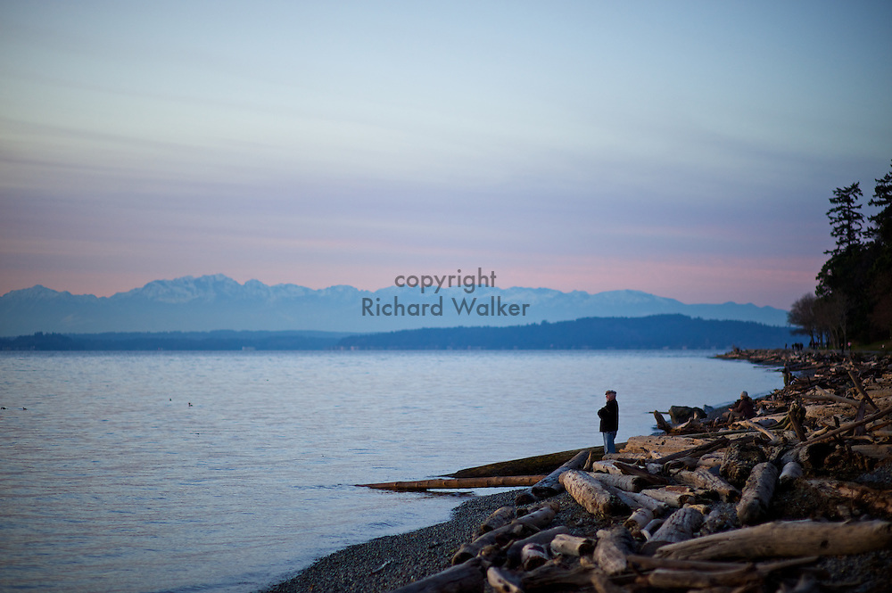 2011 January 03 - A man looks out over Puget Sound at sunset on the shores of Lincoln Park, West Seattle, WA. CREDIT: Richard Walker