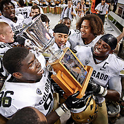 SHOT 9/1/13 7:41:57 PM - Colorado's Chidera Uzo-Diribe #96 and Derrick Webb #1 hold the trophy after winning the 2013 Rocky Mountain Showdown against Colorado State at Sports Authority Field at MiIe HIgh Stadium in Denver, Co. Colorado won the annual in-state rivalry 41-27. (Photo by Marc Piscotty / © 2013)