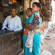 CAPTION: Using a loan from his local self-help group (SHG), Mariswamy has set up a petty shop to help cover the costs associated with his son Manu's club foot. LOCATION: Sappayyanapura (village), Kasaba (hobli), Chamrajnagar (district), Karnataka (state), India. INDIVIDUAL(S) PHOTOGRAPHED: From left to right: Mariswamy, Manu and Meelamma.