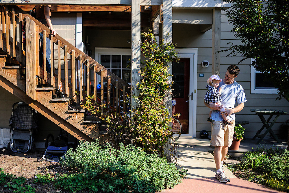 photo by Matt Roth..Jared Marx carries his daughter Beatrice, 1, right, while his wife Kit Slack slowly descends the steps with their two-year-old Nora at the start of their morning walk at the Takoma Village Cohousing complex in Washington, D.C., Saturday, September 22, 2012.