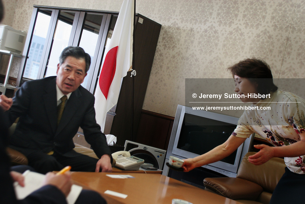 An assistant brings tea for Kazuhiko Takeshima, Chairman of Japan Fair Trade Commission, in his office, Tokyo, Japan on Monday, Apr. 24th 2006. During interviews it is common for female assistants to enter the rooms silently , bringing refreshment drinks of green tea, coffee, or orange juice, to the company head and his guests.
