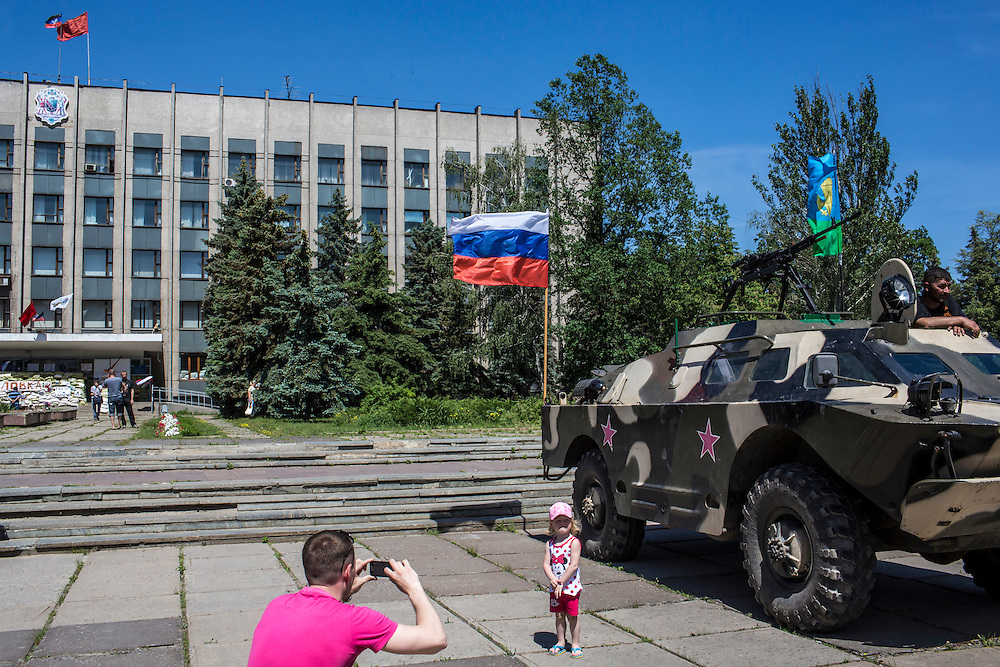 HORLIVKA, UKRAINE - MAY 24: A man photographs his daughter in front of an armored personnel carrier parked outside the occupied city administration building on May 24, 2014 in Horlivka, Ukraine. Presidential elections are scheduled for tomorrow, but pro-Russia militias have been seeking to prevent them from being administered throughout the eastern part of the country. (Photo by Brendan Hoffman/Getty Images) *** Local Caption ***
