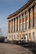 "The Royal Crescent is a residential road of 30 houses, laid out in a crescent, in the city of Bath, England. Designed by the architect John Wood the Younger and built between 1767 and 1774, it is among the greatest examples of Georgian architecture to be found in the United Kingdom and is a grade I listed building...Wood designed the great curved façade of what appears to be about 30 three storey houses with Ionic columns on a rusticated ground floor. The columns are 30 inches (76 cm) in diameter reaching 47 feet (14.3 m) and there are 114 in total, each with an entablature 5 feet (1.5 m) deep. The central house has two sets of coupled columns. Each purchaser bought a certain length of the façade, and then employed their own architect to build a house to their own specifications behind it; hence what appears to be two houses is sometimes one. This system of town planning is betrayed at the rear of the crescent: while the front is completely uniform and symmetrical, the rear is a mixture of differing roof heights, juxtapositions and fenestration. This ""Queen Anne fronts and Mary-Anne backs"" architecture occurs repeatedly in Bath..It was originally called just The Crescent and the adjective Royal was added at the end of the 18th century after Prince Frederick, Duke of York and Albany had lived at numbers 1 and 16...The Royal Crescent is constructed from Bath Stone is a Limestone comprising granular fragments of calcium carbonate its warm, honey colouring gives the  circus and much of Bath its distinctive appearance...VIEW MORE IMAGES of Royal Crescent, Bath, England, by Architect John Wood the Younger here"