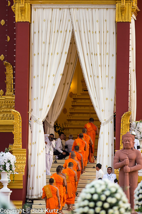"03 FEBRUARY 2013 - PHNOM PENH, CAMBODIA:   Buddhist monks file into the crematorium for the final Buddhist chanting service for former Cambodian King Norodom Sihanouk in the crematorium built for the King's funeral at the National Museum in Phnom Penh. Norodom Sihanouk (31 October 1922 - 15 October 2012) was the King of Cambodia from 1941 to 1955 and again from 1993 to 2004. He was the effective ruler of Cambodia from 1953 to 1970. After his second abdication in 2004, he was given the honorific of ""The King-Father of Cambodia."" He served as puppet head of state for the Khmer Rouge government in 1975-1976, before going into exile. Sihanouk's actual period of effective rule over Cambodia was from 9 November 1953, when Cambodia gained its independence from France, until 18 March 1970, when General Lon Nol and the National Assembly deposed him. Upon his final abdication in 2004, the Cambodian throne council appointed Norodom Sihamoni, one of Sihanouk's sons, as the new king. Sihanouk died in Beijing, China, where he was receiving medical care, on Oct. 15, 2012. His cremation will take place on Feb. 4, 2013. Over a million people are expected to attend the service.   PHOTO BY JACK KURTZ"