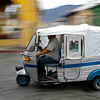 Antigua Guatemala, Guatemala 25 May 2008<br /> A Tuk-Tuk passes by in Antigua Guatemala city.<br /> La Antigua is among the world's best conserved colonial cities. <br /> It is located in the central highlands of Guatemala, famous for its well-preserved Spanish Colonial and Baroque architecture as well as a number of spectacular ruined churches. It has been designated a UNESCO World Heritage Site.<br /> Photo: Ezequiel Scagnetti