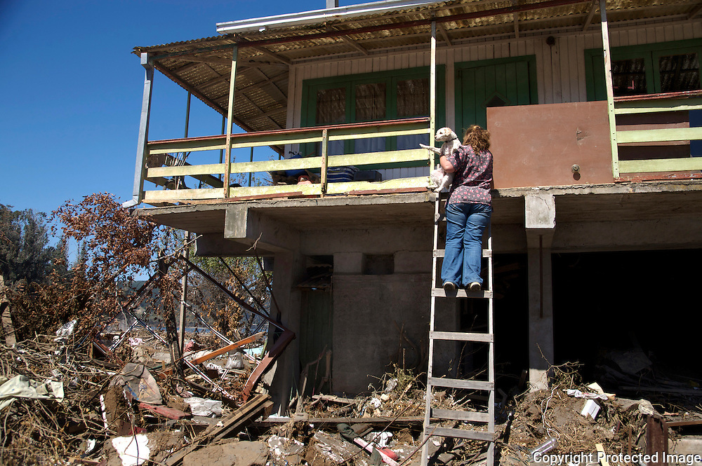 Woman exits her house by way of ladder in Constitución, Chile. This was one of the only houses on the beach not destroyed by the earthquake, or taken by the waves from the Tsunami.