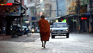 A Buddhist monk walks at sunrise on the street in Mae Sot, Thailand on Friday, November 16, 2007. Local residents offer monks food and gifts as they make their way to a local wat (temple) every morning.