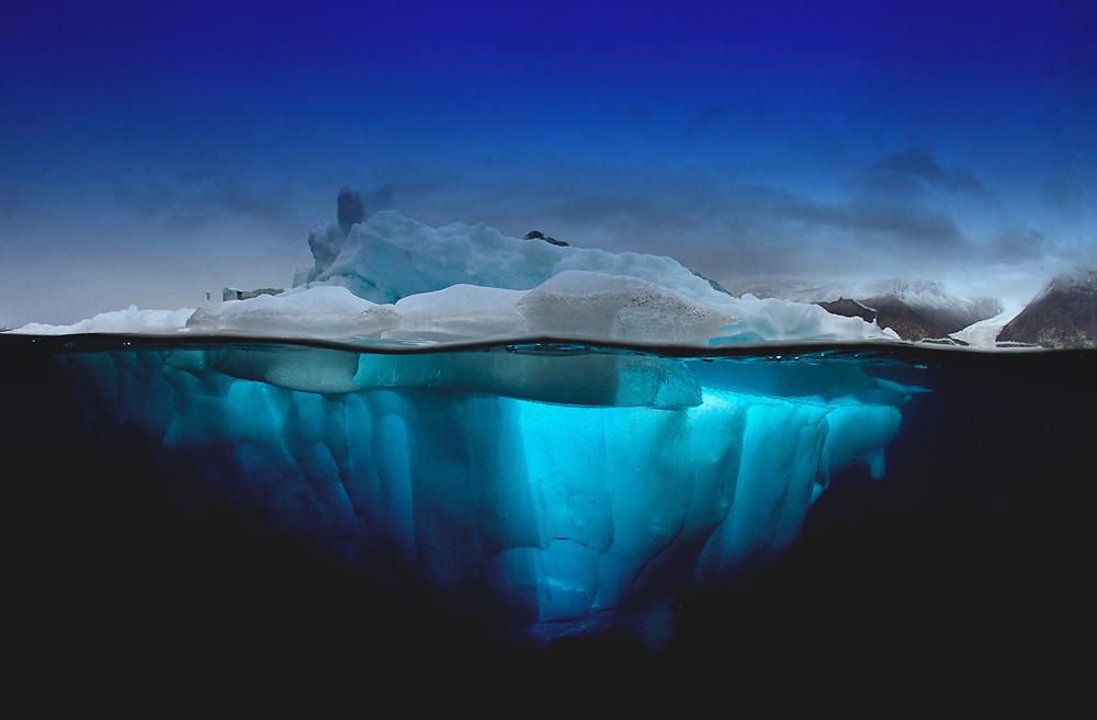 Iceberg at Norvestfjord with glacier valley, Greenland
