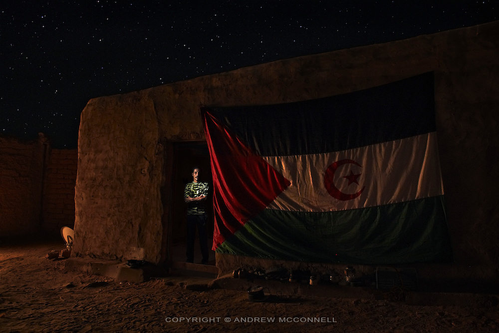 Ihaka Sidahmad Embark, 34, musician, pictured in 27th of February refugee camp, Algeria...I was born in El Aaiún in 1975. I remember when my mother had to find food for us because the Moroccans catch my father. I was just six. We didn't know if he was alive or dead, they held him from 1981 to '91. I remember he went out and said he would be back very soon and I did not see him for ten years. He was arrested because he used to talk about independence and was a Polisario artist. ..I was in a music group, 'Stars of the Saguia el Hamra.' After a while a lot of Saharawis liked us. We had some songs talking about the Saharawi cause, with messages for the Saharawi people, but in a subtle way. But some Saharawi people working with the Moroccan government told them about the songs and then the group couldn't live there and play anymore, the Moroccans were going to arrest us. Two guys from the group left on a small boat to the Canary Islands. It was in December 2000. I was living in a house and couldn't go outside, a member of my family said he could take me to the wall. There were two friends who were going to cross with me. We knew it was like going towards fire but after the fire there would be water and anyway living there [in El Aaiún] was fire.  ..We drove to outside of Smara and walked for one day. At night we could see the Moroccan soldiers on the wall. The wall is really four small walls, if you have no information about the wall you cannot cross it. We crossed the first wall on a hill and found ourselves in a trench, we crossed this then the second wall, we heard dogs and knew the base was near. We found ourselves at the last wall and didn't realise we had crossed the third wall. We heard dogs on each side so knew the bases where there so we couldn't go any other way.  We came across a base in the hills one hundred metres away. We stopped, we couldn't speak or smoke. We watched and saw no soldiers so we knew they were sleeping, we started walking very slowly, then w