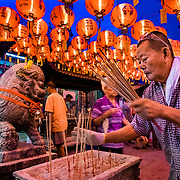 A man collects the old joss sticks, or incense at the Temple of Mercy in Georgetown, Penang, Malaysia.