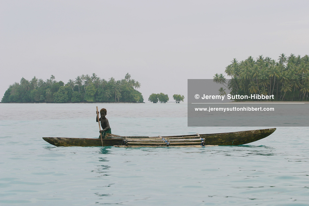 A child paddles his wooden canoe in the lagoon waters beside the two islands which make up Huene Island ( the island was split in two by sea erosion of the land in the 1970's), on the Carterets Atoll, Papua New Guinea, on Monday, Dec. 11, 2006.  Rising sea levels have eroded much of the coastlines of the low lying Carteret islands (situated 80km from Bougainville island, in the South Pacific), and waves have crashed over the islands flooding and destroying what little crop gardens the islanders have. Food is in short supply, banana and swamp taro crops are failing due to the salt contamination of the land, and the islanders live on a meagre one meal per day diet of fish and coconut. There is talk by the Autonomous Region of Bougainville government to relocate the Carteret Islanders to Bougainville island, but this plan is stalled due to a lack of finances, resources, land and coordination.