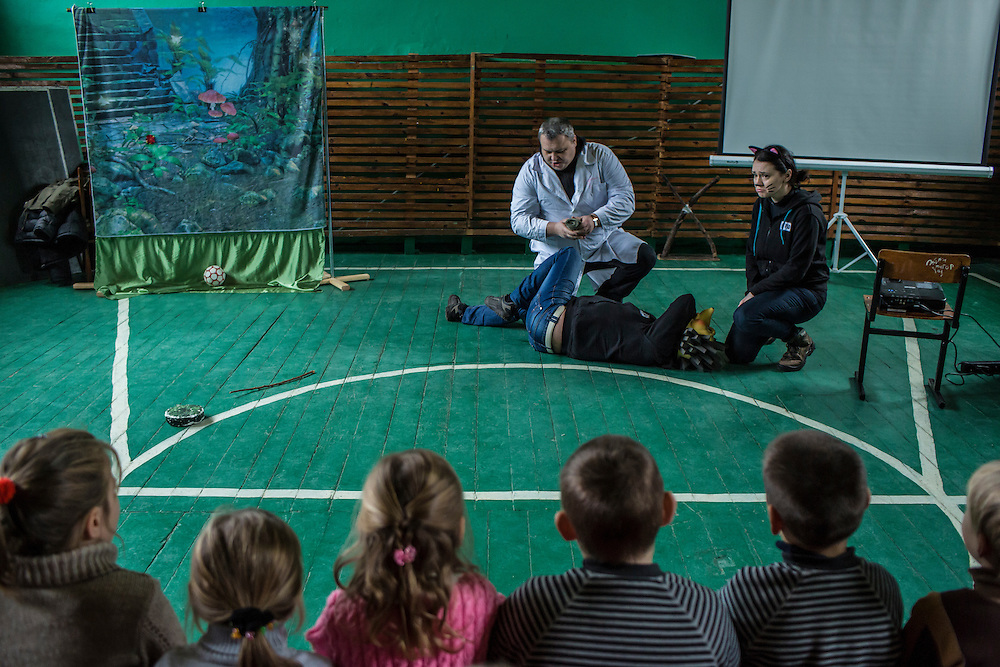 Olena Rozvadovska and other employees of the Swiss Foundation on Mine Action gives a mine awareness training at School #21 on Tuesday, December 15, 2015 in Scherbynivka, Ukraine.