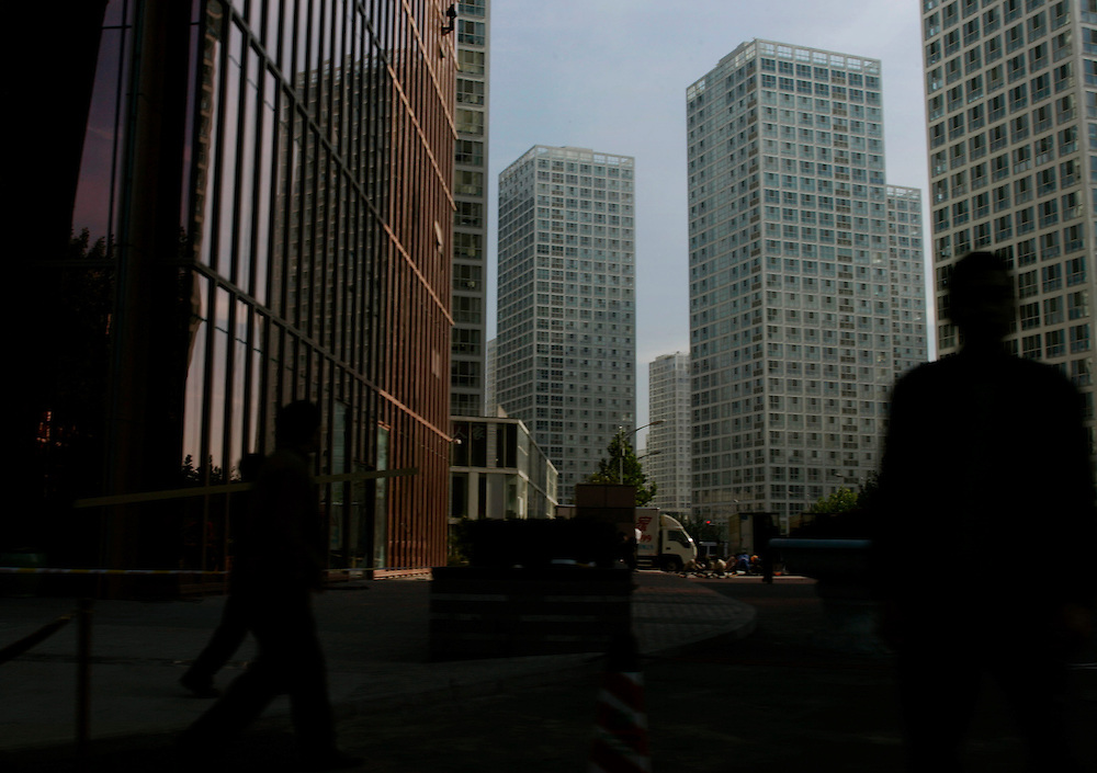 Pedestrians walk along side high rises in Beijing, China, Tuesday, Oct. 28, 2008. Block after city block, towers of concrete, steel and glass fill the skyline teeming and congested, the intensely urban landscapes of China's biggest cities show a glimpse of what the future will hold for the rest of the country. In the sprawling megacities of Beijing, Shanghai and Chongqing, where populations exceed 10 million people, extreme urban density means that the number of people living within a few square blocks here is equal to the population of entire mid-size U.S. cities. China's urban population soared to 607 million people last year _ nearly equaling the 700 million living in the countryside. The country's headlong plunge toward urbanization continues unabated as tens of millions of migrants from the countryside flood to cities in search of money, jobs and other opportunities.