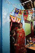 A relation of the bride looks out from the doorway to her home. Ratnam Road.