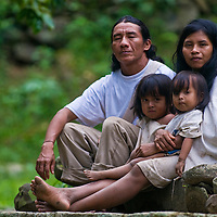 """TAYRONA PARK , COLOMBIA - DECEMBER 17 2010 : Indian family sit together at home in a village in """"Tayrona"""" park , Colombia"""