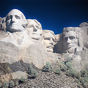 The Mount Rushmore National Memorial, near Keystone, South Dakota, is a monumental granite sculpture by Gutzon Borglum. The monument represents the first 150 years of the history of the United States of America with 60-foot (18m) sculptures of the heads of former United States presidents (left to right): George Washington, Thomas Jefferson , Theodore Roosevelt, and Abraham Lincoln. The entire memorial covers 1,278.45acres (5.17km2) and is 5,725feet (1,745m) above sea level...This is a digital combination of an infrared image and a visible color image.  The color picture is used to colorize the infrared image giving a foreign and new perspective.  Plants and trees reflect more infrared light and appear brighter in images while the sky reflects less making it darker.
