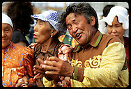 Man in gold shirt leads chant in ritual osuokhai circle dance @ midsummer Ysyakh fest; Yakutsk Russia