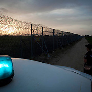 Police officers stand guard at the 12.5-kilometer barbed-wire fence along the land border with Turkey, which was met with skepticism at home as well as from many EU officials.  It has allegedly succeeded in blocking one of the most popular transit routes for migrants seeking to make their way to the West.  Image © Angelos Giotopoulos/Falcon Photo Agency