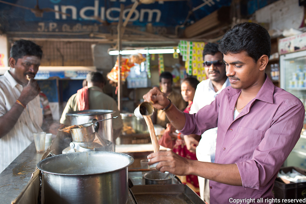 Strong, espresso like drip coffee is added to hot milk in a stall in Chennai, Tamil Nadu, India