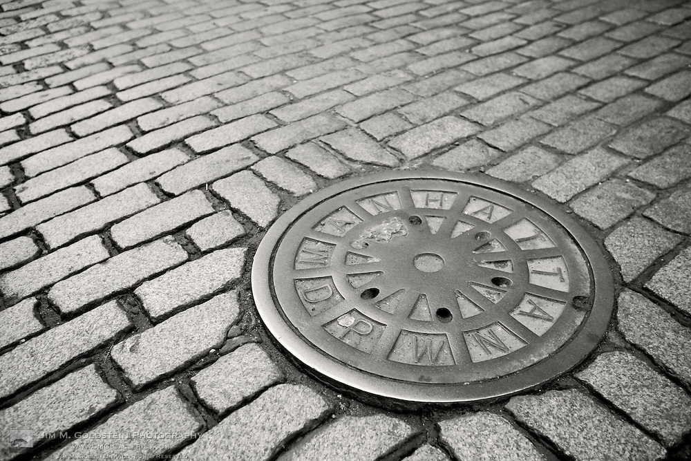 A low view of a New York city manhole on a cobblestone paved street in the SoHo district of Manhattan.