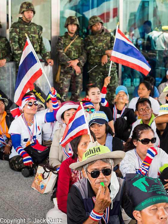 "08 APRIL 2014 - BANGKOK, THAILAND:  Anti-government protestors sitting in front of Thai soldiers block the entrance to the Ministry of Justice in Bangkok. Several hundred anti-government protestors led by Suthep Thaugsuban went to the Ministry of Justice in Bangkok Tuesday. Suthep and the protestors met with representatives of the Ministry of Justice and expressed their belief that Thai politics need to be reformed and that corruption needed to be ""seriously tackled."" The protestors returned to their main protest site in Lumpini Park in central Bangkok after the meeting.    PHOTO BY JACK KURTZ"