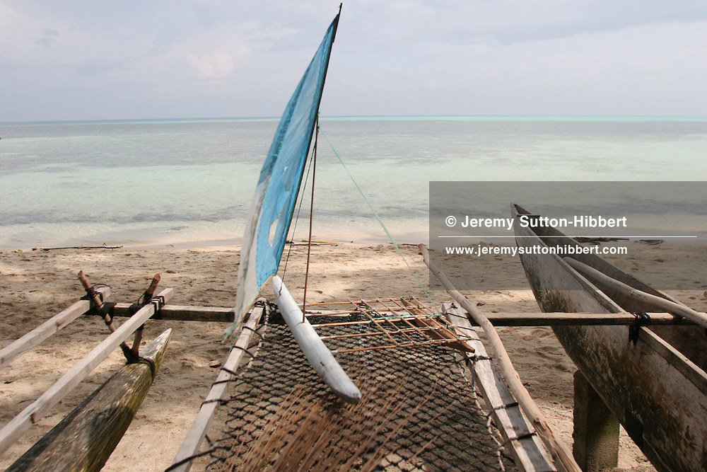 A toy canoe with sail sitting on top of a real canoe and outrigger, Iangain Island, Carterets Atoll, Papua New Guinea, on Tuesday, Dec. 12, 2006. Rising sea levels have eroded much of the coastlines of the low lying Carteret islands (situated 80km from Bougainville island, in the South Pacific), and waves have crashed over the islands flooding and destroying what little crop gardens the islanders have. Food is in short supply, banana and swamp taro crops are failing due to the salt contamination of the land, and the islanders live on a meagre one meal per day diet of fish and coconut. There is talk by the Autonomous Region of Bougainville government to relocate the Carteret Islanders to Bougainville island, but this plan is stalled due to a lack of finances, resources, land and coordination.