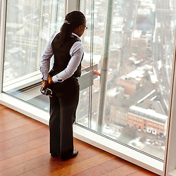 London, UK - 23 January 2013: a hostess looks at the panorama of London as seen from 'The View from the Shard'.  'The View from the Shard' opens to the general public on the 1st of February, offering an unrivalled view on the city of London.
