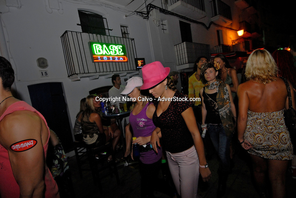 Young people in the Marina port area of Ibiza, where many bars open until its time to go to the clubs and party promotional parades attract people´s attention. Ibiza, Spain