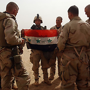 U.S. Army 3rd Infantry Division 3-7 infantry Corporal Charles Johnson, (L) from Myrtle Beach, South Carolina, shows his squad an Iraqi flag captured during an raid on a Iraqi border post late the day before March 21, 2003.