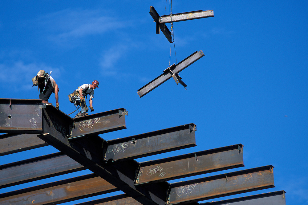 USA, Washington, Seattle, Construction workers bolt steel beams onto frame of office tower near International District
