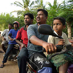 Left to right, Judeson Britto Moses, Richard Speck and his son Terren Speck, 6, ride motorcycles with other residents of Dutch Bar village to the site where government officials say they will move their town, Batticaloa, Sri Lanka, Jan. 15, 2005. Residents of the small Christian village spent more than six weeks in a makeshift refugee camp at the local convent recovering from the devastating tsunami that hit the eastern and southern borders of Sri Lanka. They were then moved into another temporary living camp, while awaiting the building of new homes.