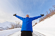 A male jogger jogging holds up his arms and expresses exuberance at the sunny blue-sky weather along Hiland Road in South Eagle River with the Chugach Mountains and Chugach State Park in the background in Southcentral Alaska. Winter. Afternoon. MR.