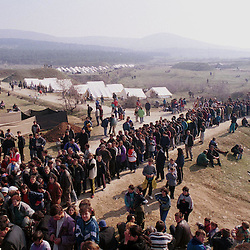 Ethnic Albanian refugees from Kosovo wait to receive food at a camp set up by French and English military from NATO near Skopje, Macedonia Wednesday, April 7, 1999. The camp has helped to alleviate the crisis at the border camp in Blace where hundreds of people died.  (Photo by Ami Vitale)