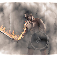 Muscular male with sword and shield in Roman environment. Fire coming out of veins down arm onto sword.